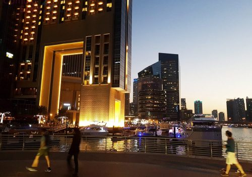People walking on Dubai Marina in the evening